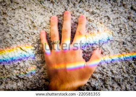 Hand crossed by rainbow generated from sun flares - stock photo