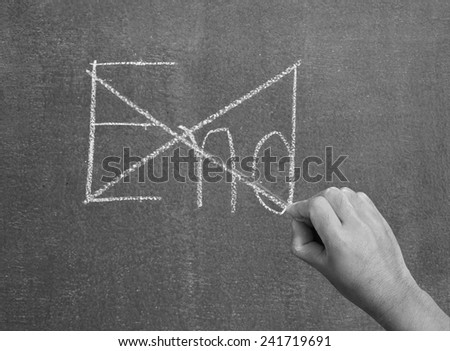 Hand crosses the end on the chalkboard. - stock photo