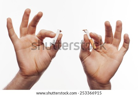 Hand crushing cigarette over white background - stock photo