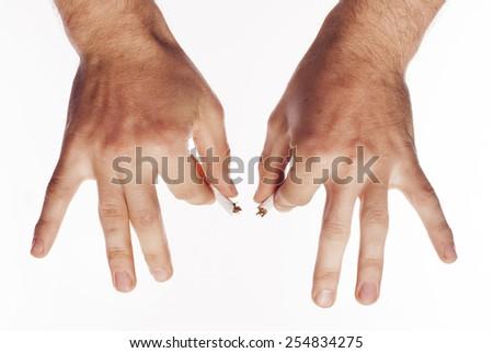 Hand crushing cigarette over white background - stock photo