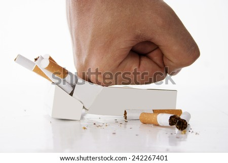 Hand crushing cigarettes over white background - stock photo