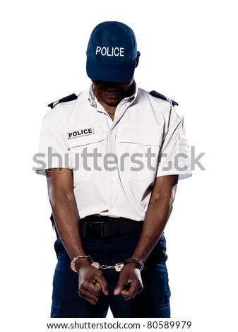 Hand cuffed police officer with head down standing on white isolated background - stock photo