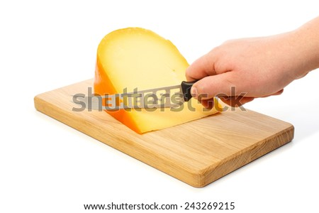 Hand cuts with cheese knife the Dutch Gouda cheese on a cutting board - stock photo