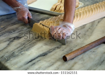 Hand cutting fudge on a large marble slab - stock photo