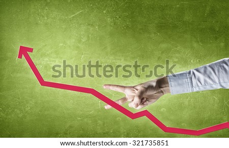 Hand cutting with fingers rising arrow representing business growth