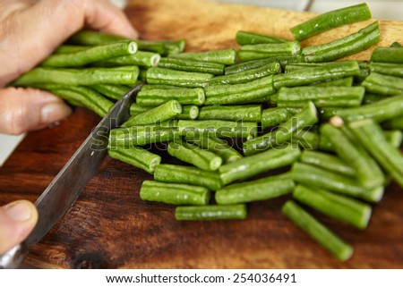 Hand cutting yardlong bean as ingredient for cooking - stock photo