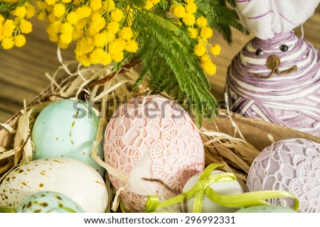 Hand decorated Easter Eggs and speckled birds eggs in straw with a branch of colorful yellow clusters of mimosa flowers in a natural country Easter background - stock photo