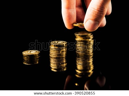 hand deliver a stack of coins in the form of a graph profit growth on a black background - stock photo