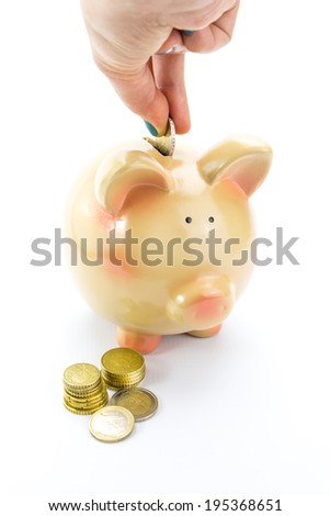 Hand depositing coins into piggy bank isolated on white