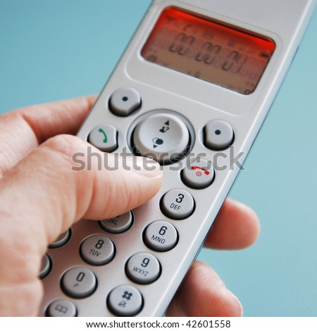 hand dialing the phone in front of green background