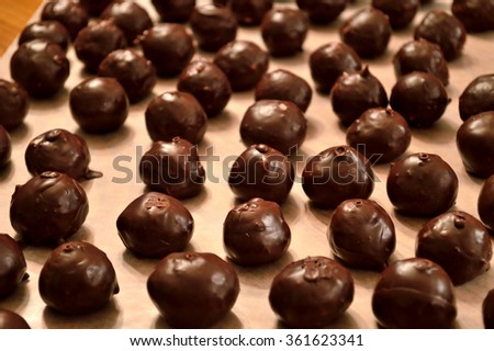 Hand-dipped, chocolate Martha Washington candy (also know as chocolate bon-bons) layed out on wax paper in rows to dry.