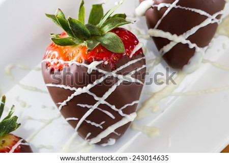 hand dipped strawberries in dark chocolate with a drizzle of white chocolate for a garnish - stock photo