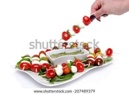 Hand dipping a skewer of cherry tomatoes and mozzarella in a vinaigrette sauce, isolated on white - stock photo