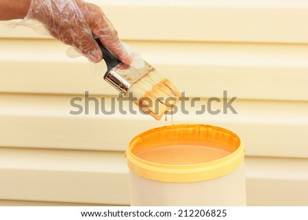 hand dipping paint brush into a can of wood stain  - stock photo
