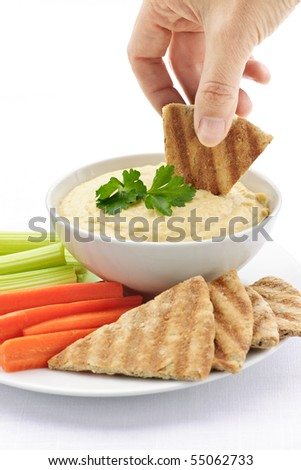 Hand dipping slice of pita bread into bowl of hummus - stock photo