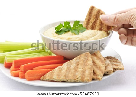 Hand dipping slice of pita bread into bowl of hummus
