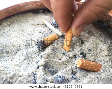 Hand discarded cigarette into the ashtray, quitting smoking conceptual. Cigarette butts. - stock photo