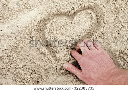 Hand draw heart in the wet sand on the coast  - stock photo