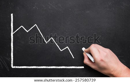 hand drawing a decreasing chart on a blackboard - stock photo