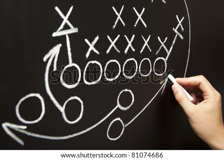 Hand drawing a game strategy with white chalk on a blackboard. - stock photo