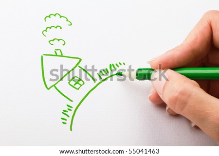 Hand drawing a house with green pen - stock photo