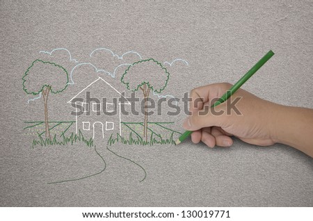 hand drawing a house with green pencil on fabric - stock photo