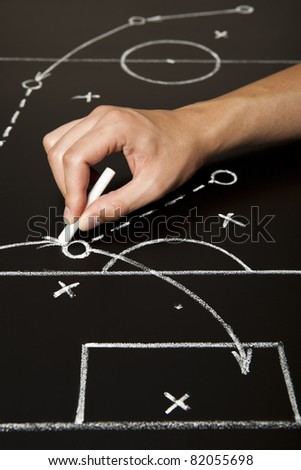 Hand drawing a soccer game strategy with white chalk on a blackboard. - stock photo