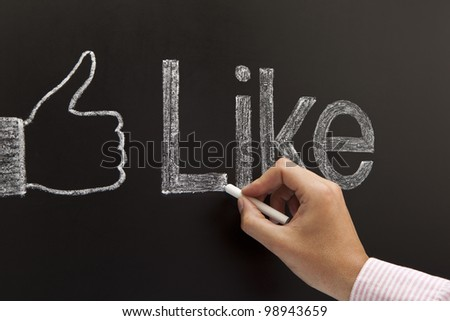 Hand drawing a thumbs up sign with the word Like on a blackboard with white chalk. - stock photo