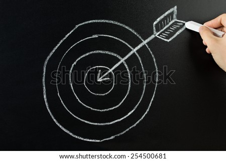 Hand Drawing Dart And Arrow With Retargeting Word On Blackboard - stock photo
