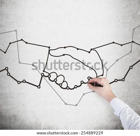 hand drawing handshake and charts on wall - stock photo