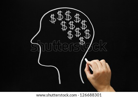 Hand drawing Human head and many dollar signs with white chalk on blackboard. - stock photo