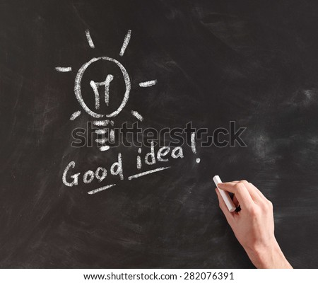 Hand Drawing Illuminated Light Bulb with Chalk on Black Board, Concept Image of Having a Great Idea - stock photo