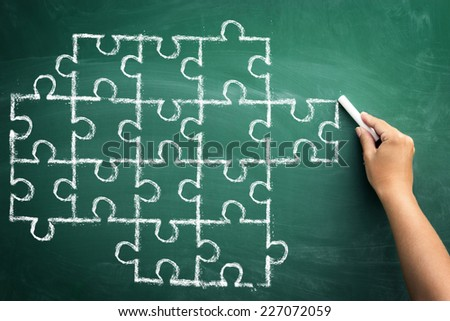 Hand drawing puzzle on blackboard to explain   - stock photo