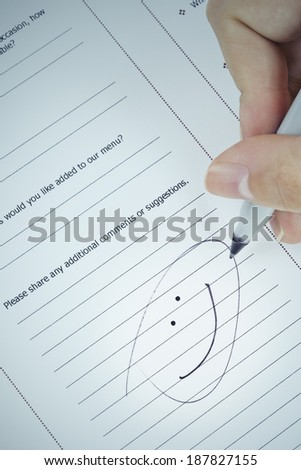 Hand drawing smiley face with black marker on service evaluation form, business feedback concept
