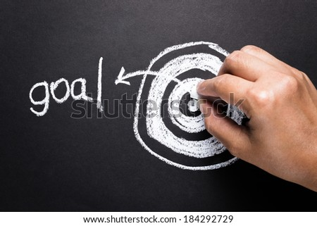 Hand drawing target dartboard with chalk for set goal concept - stock photo