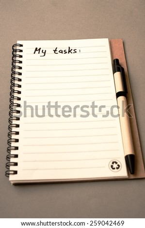 Hand drawing task list on notebook from recycling paper on grey background - stock photo