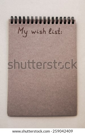 Hand drawing wish list on notebook from recycling paper on grey background - stock photo