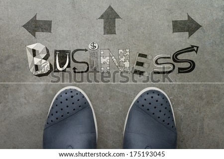 Hand drawn BUSINESS  design word on front of business man feet as concept - stock photo