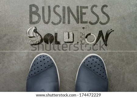 Hand drawn BUSINESS SOLUTION design word on front of business man feet as concept - stock photo