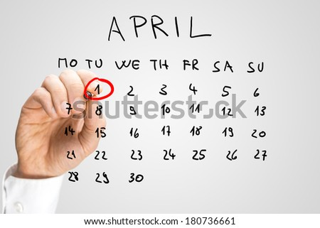 Hand drawn calendar for April on a virtual interface or screen with the First ringed in red by a man holding a marker pen, closeup of his hand. Fools day concept. - stock photo