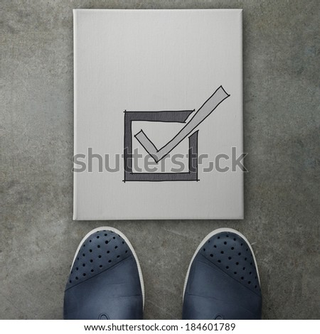 Hand drawn check mark  icon on canvas board on front of business man feet as concept  - stock photo