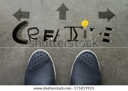 Hand drawn CREATIVE  design word on front of business man feet as concept - stock photo