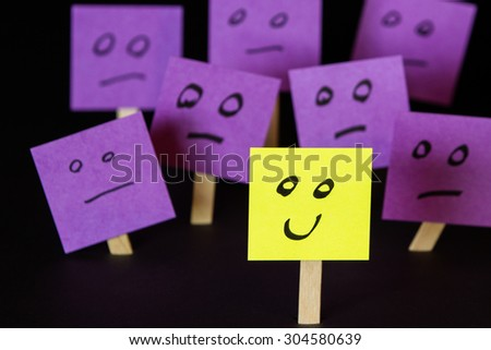 hand drawn faces on sticky notes with on that stands out in a positive way - stock photo