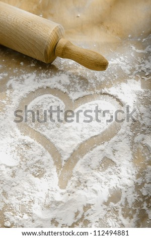 Hand drawn heart in sprinkled flour with a wooden rolling pin showing a love and enjoyment of cooking and baking - stock photo