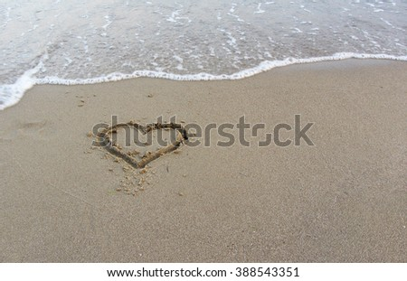 Hand drawn symbol of a heart in beach sand just under an incoming sea wave.