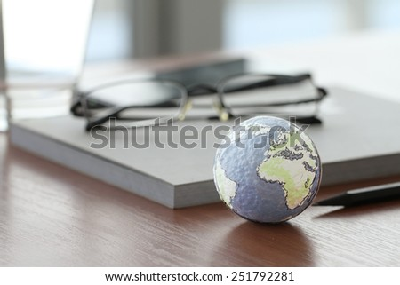 hand drawn texture globe on wood table near note book and glasses - stock photo