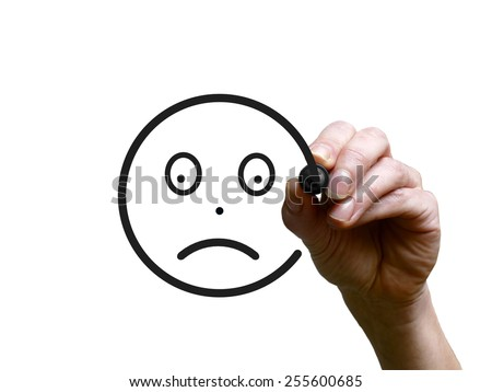 Hand draws sad face with black marker on transparent whiteboard - stock photo