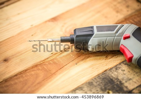 Hand Drill on Wood background, Home DIY Wokshop Concept.