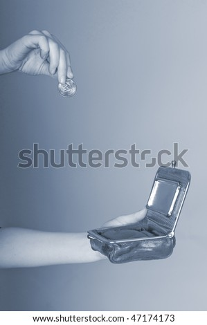 Hand dropping coin into open purse - stock photo