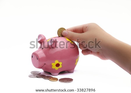 Hand dropping coins into pink piggy bank - stock photo